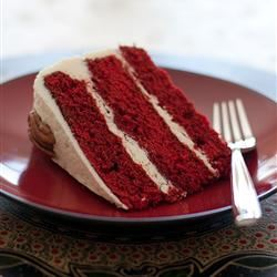 A slice of three-layer cake on a red plate