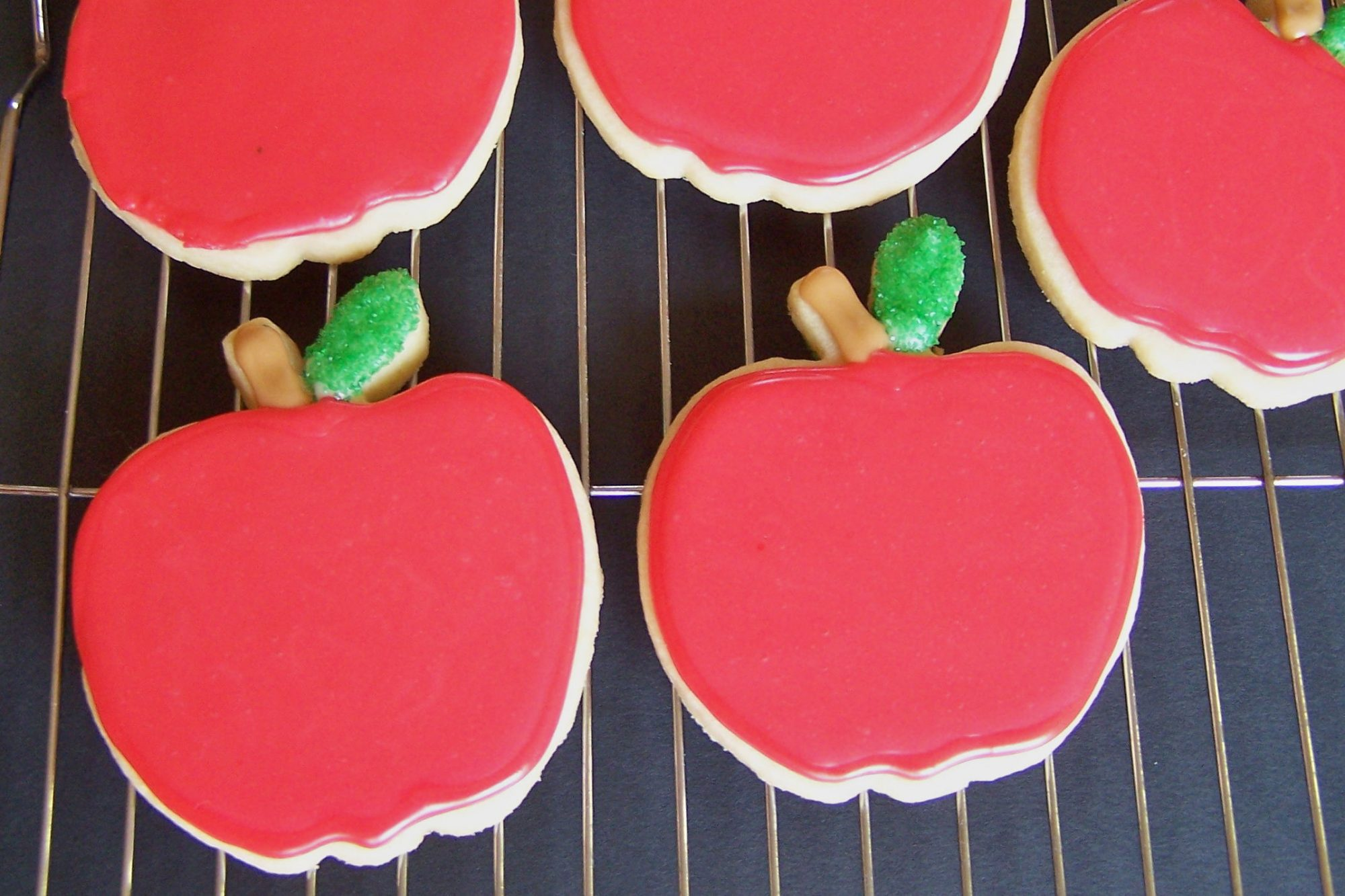 Apple-shaped cookies with red icing and green leaves
