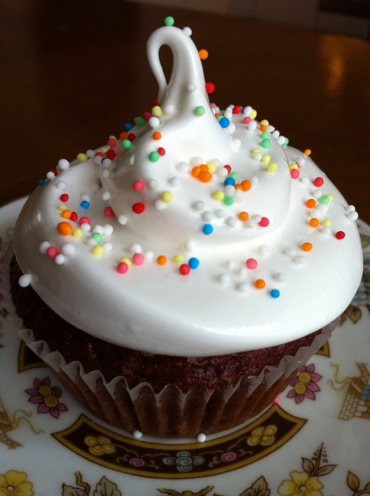 Shiny white frosting on a cupcake with colorful sprinkles