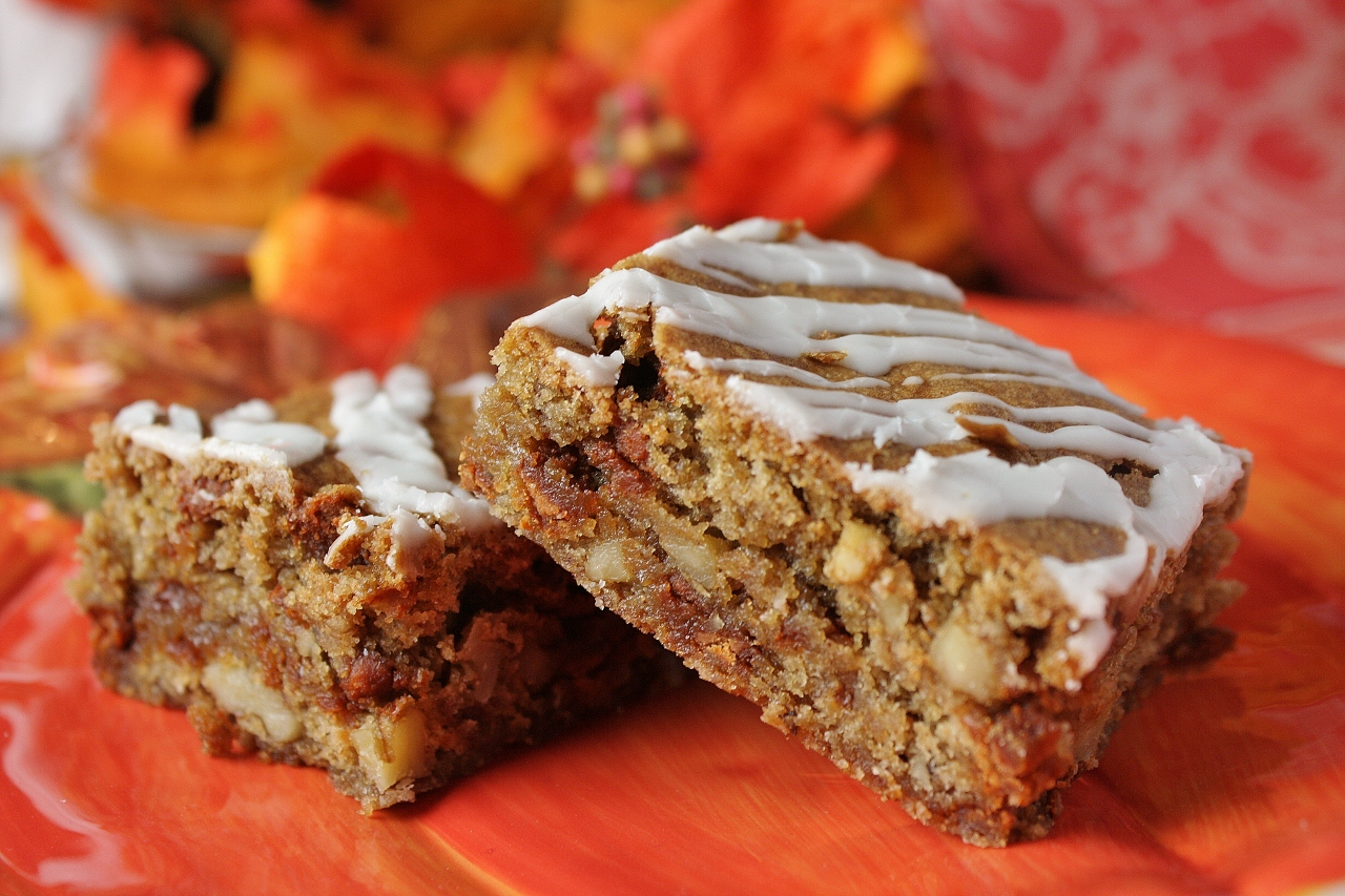 Two blonde bars with stripes of confectioners' sugar icing on an orange plate with fall leaf decor in the background