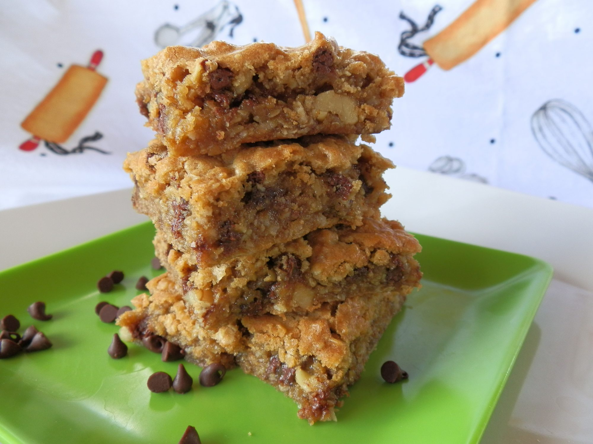 A stack of four blondies on a green square plate with scattered mini chocolate chips