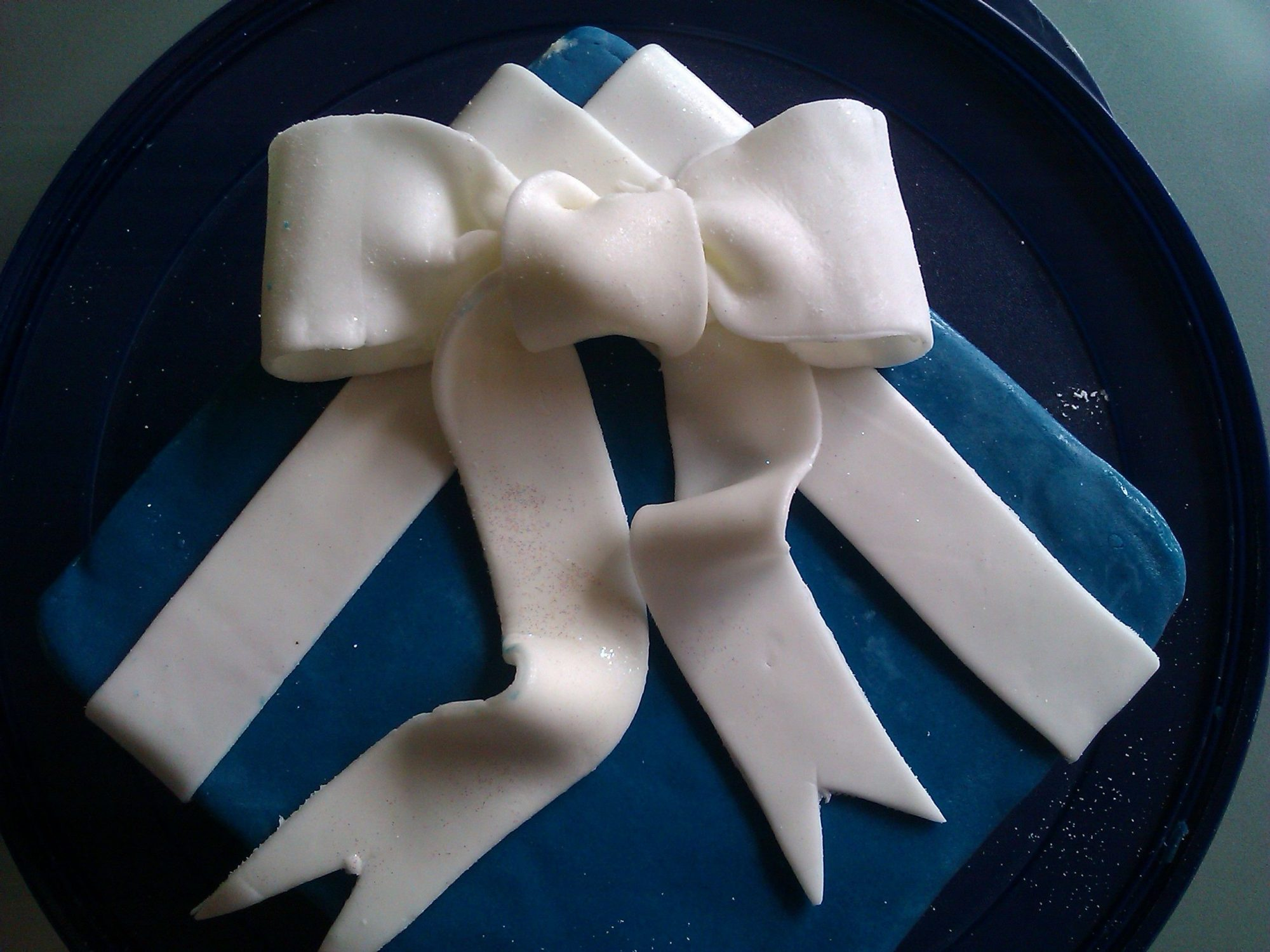 A square cake decorated to look like a blue-wrapped gift tied with a white fondant ribbon and bow