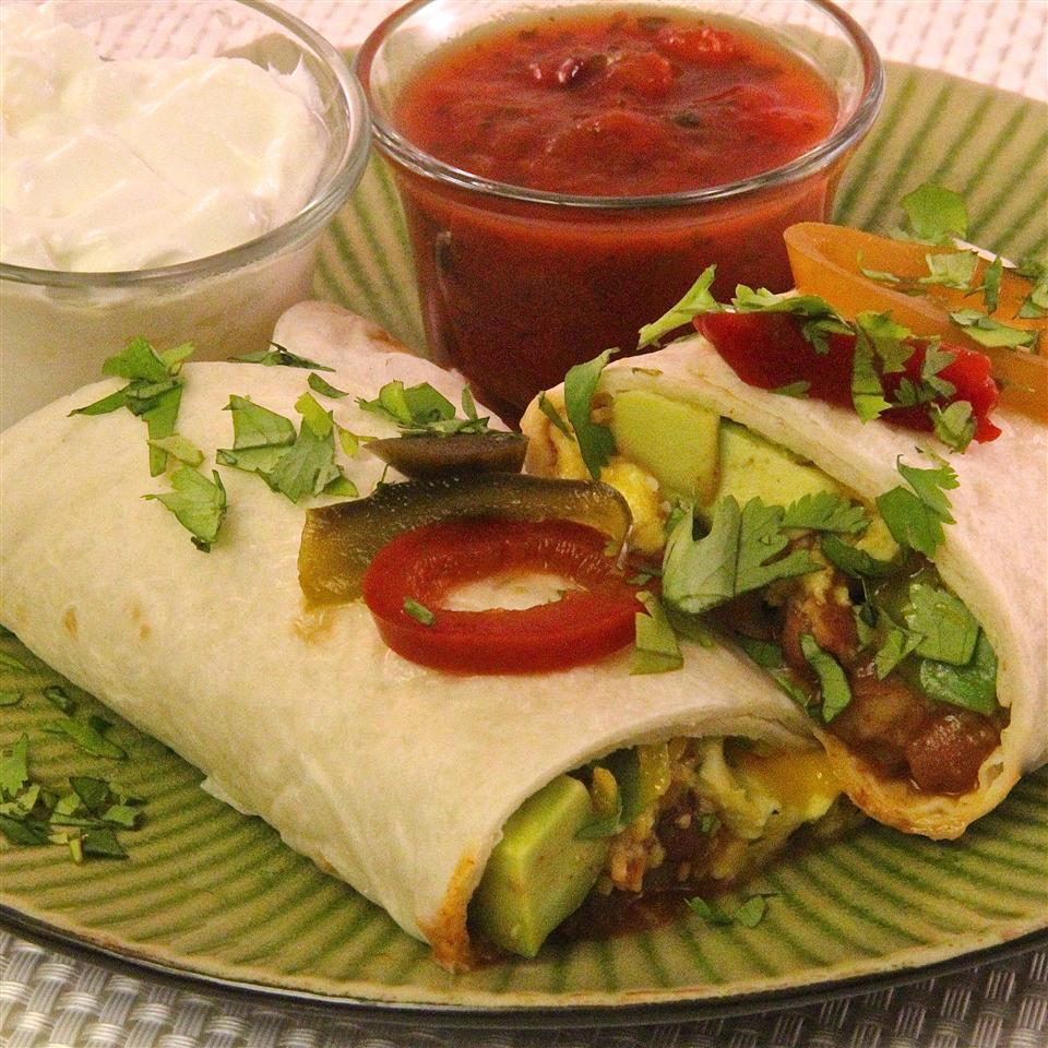 A breakfast burrito on a plate with glass ramekins of salsa and sour cream