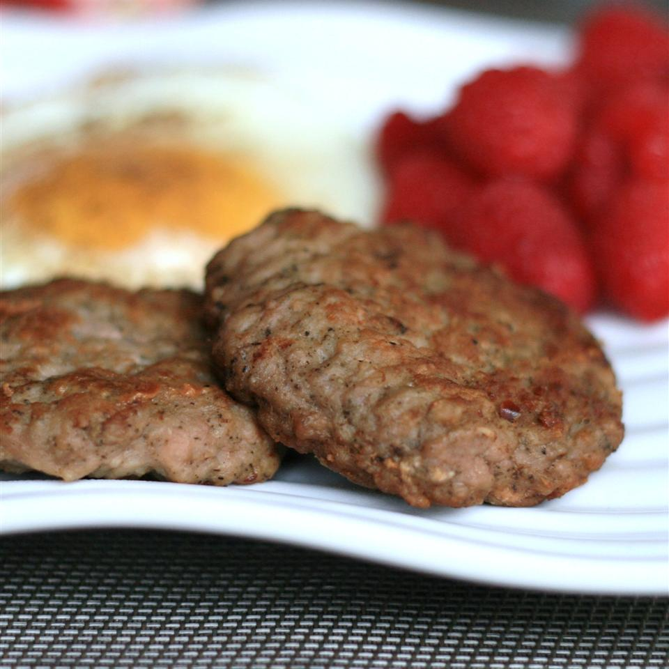 A closeup of two sausage patties on a white plate with fried eggs and fresh raspberries in the background