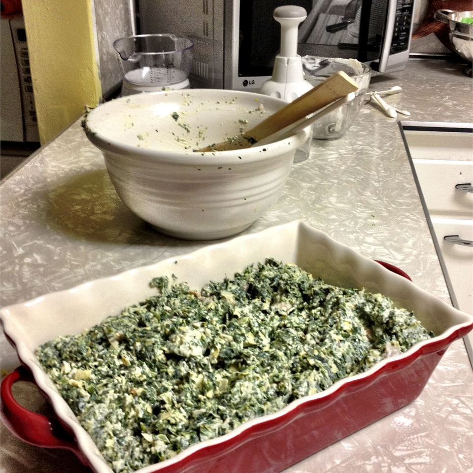 spinach artichoke casserole in a red dish on kitchen counter