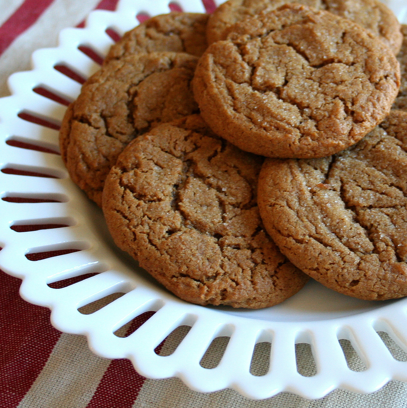a white plate with a scalloped rim holding molasses ginger cookies topped with sugar