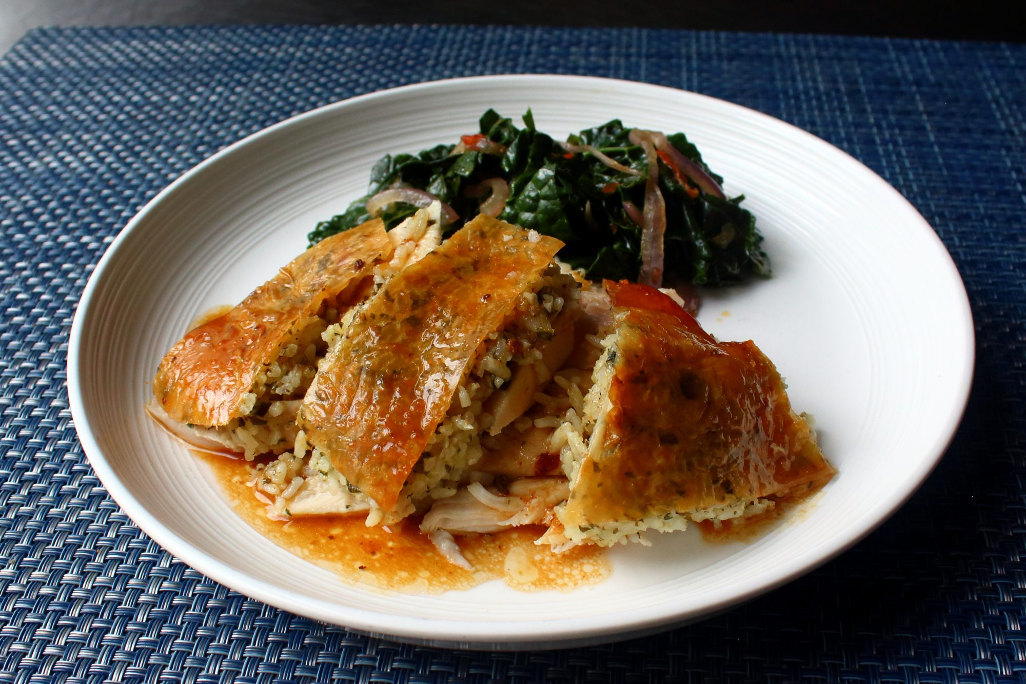 a chicken breast with rice stuffed under the crispy brown skin on a white plate , with wilted Swiss chard in the background