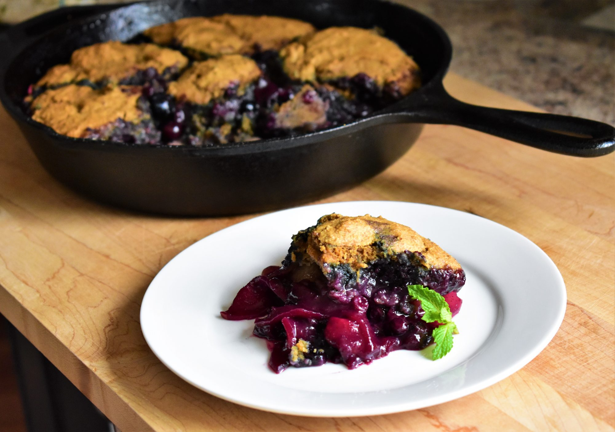 Piece of Apple-Blueberry Cobbler on white plate next to cast iron pan with cobbler