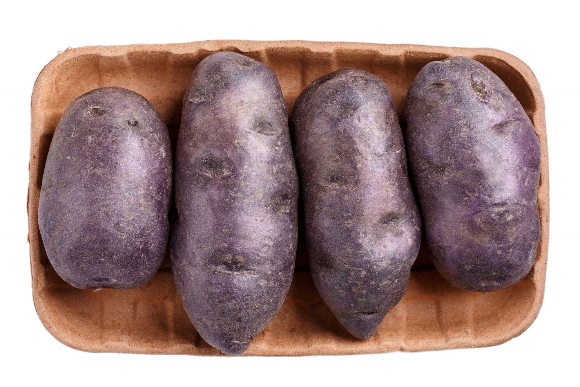 Raw purple potatoes on cardboard food tray isolated on white background. Top view.