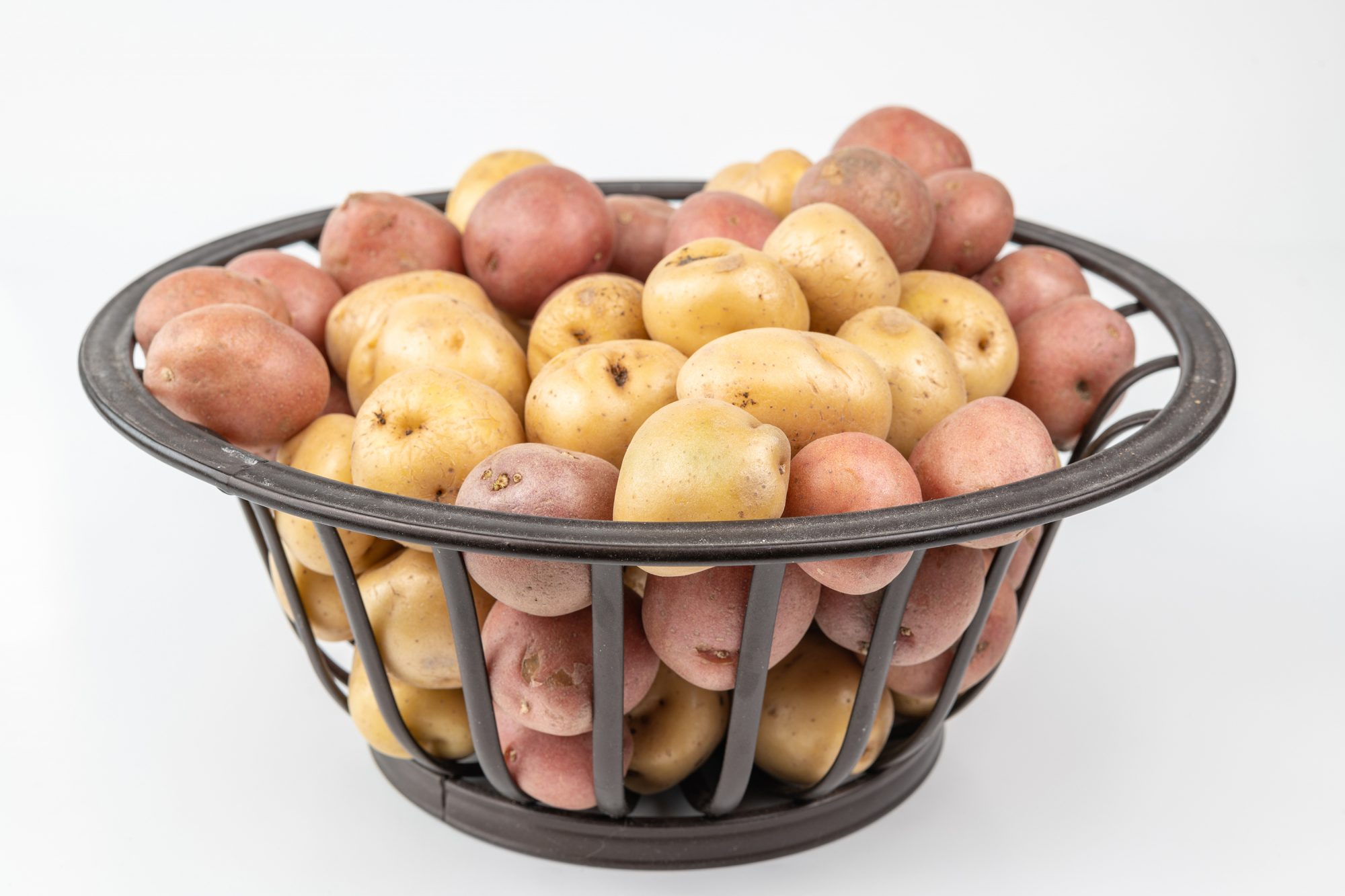Small potatoes of different colors in a container