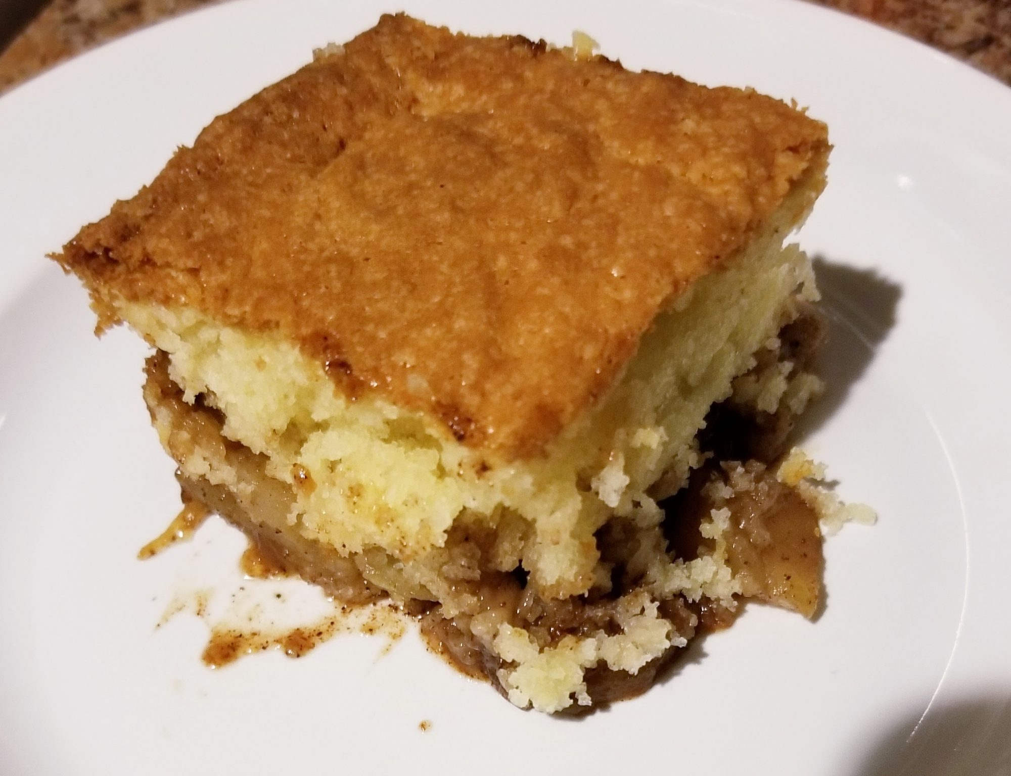 Piece of apple cobbler on white plate
