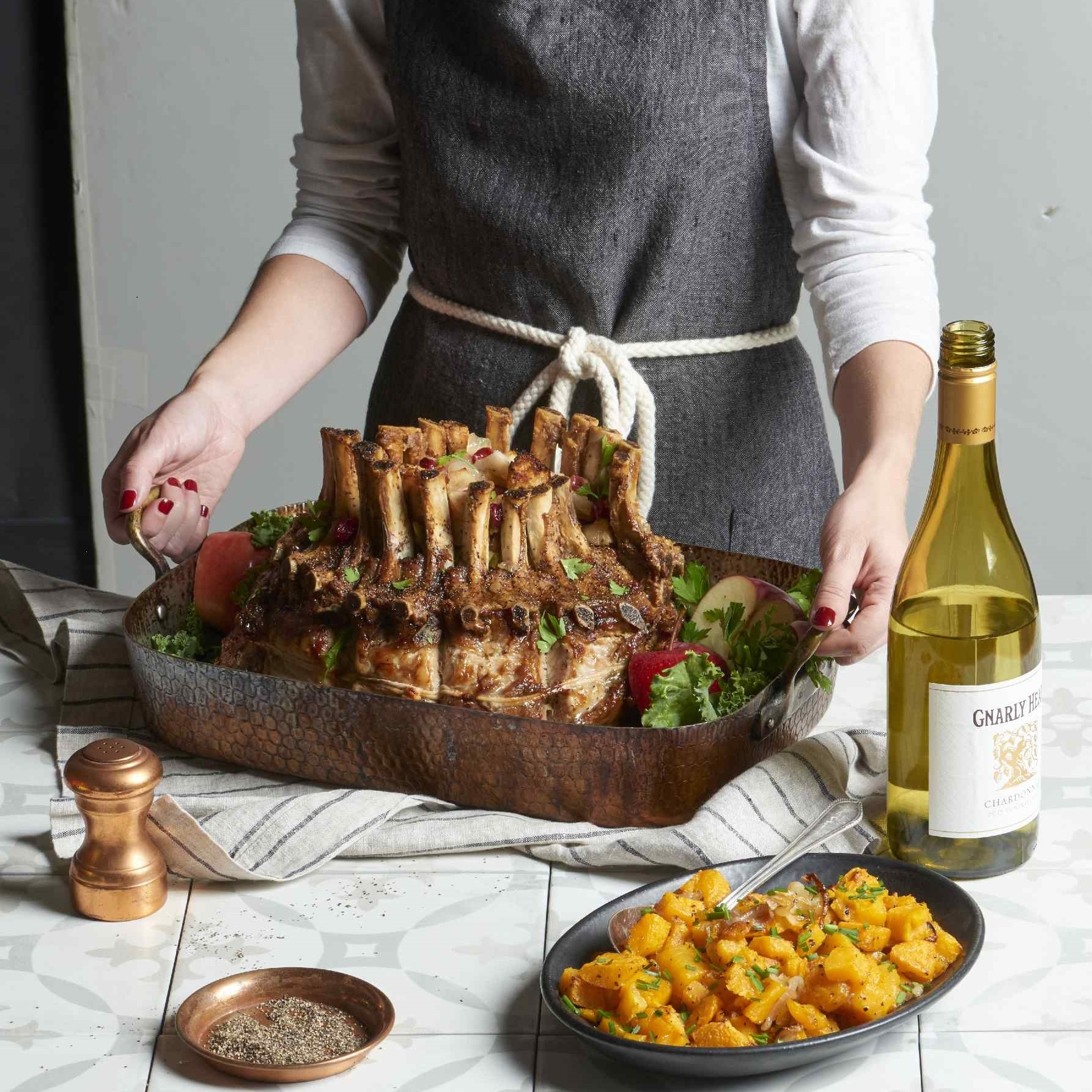 crown roast of pork in a roasting pan with side dishes