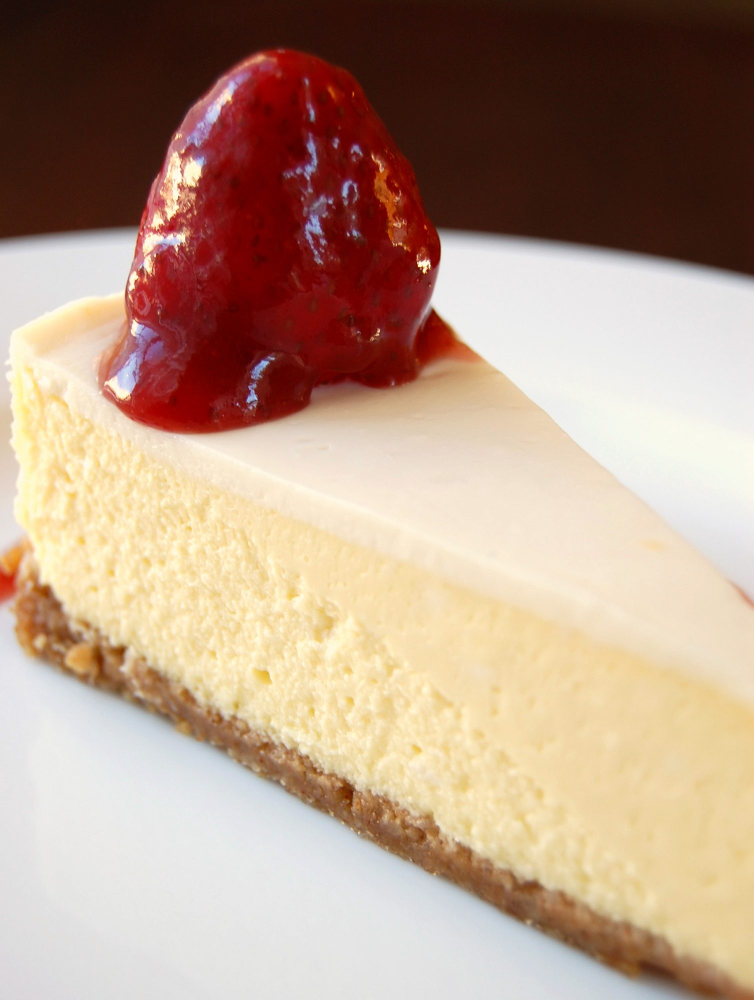 a closeup of a slice of sour cream-topped cheesecake with a fresh strawberry and glaze