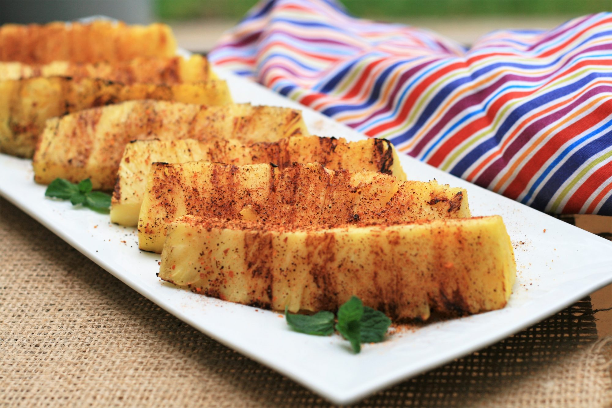 wedges of grilled pineapple on a white platter with grill marks and sprinkle of tajin seasoning