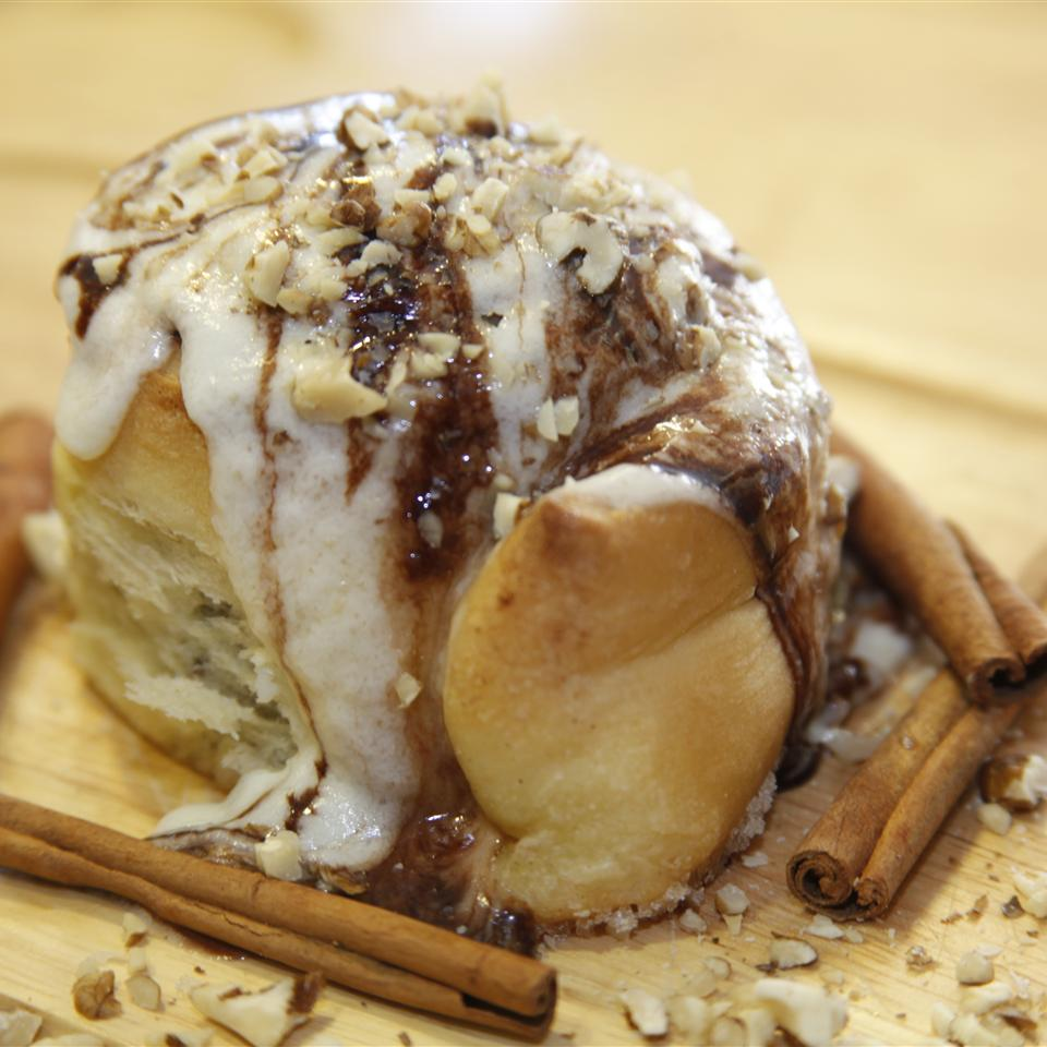 a cinnamon roll glazed with cream cheese frosting and topped with chopped walnuts, garnished with cinnamon sticks