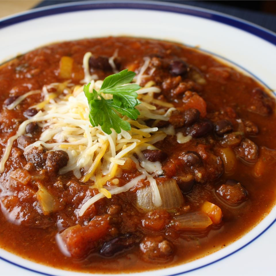 a closeup view of a bowl of beef and bean chili garnished with shredded cheese and a parsley leaf
