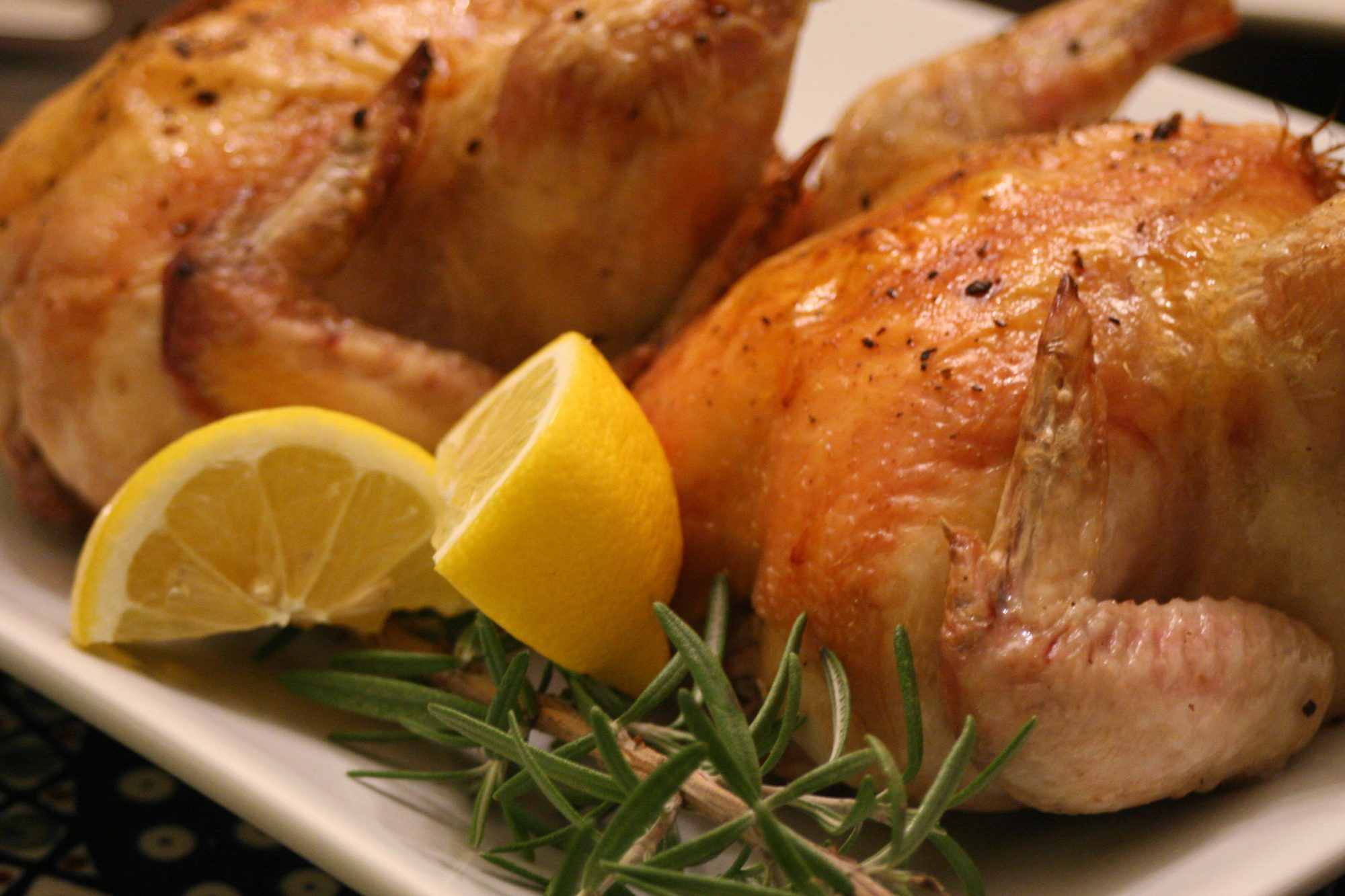 a closeup of two roast Cornish hens on a white platter garnished with lemon wedges and fresh rosemary