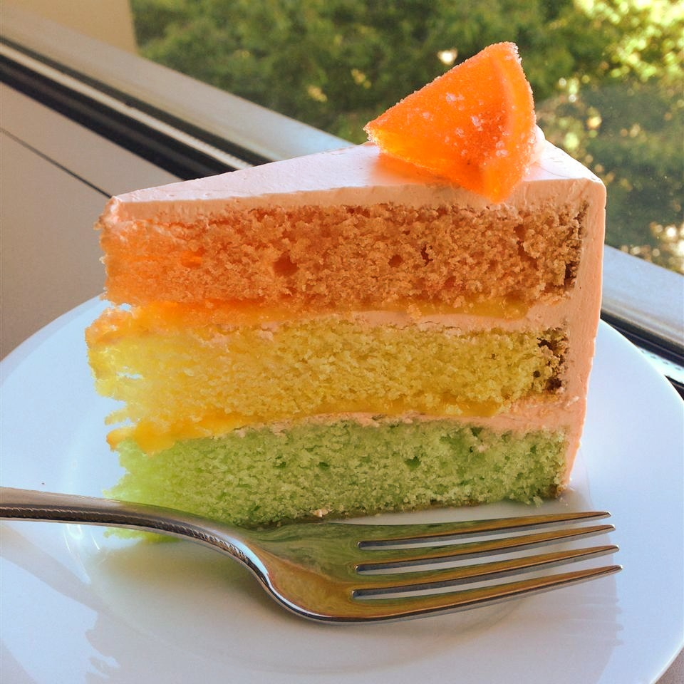 slice of citrus rainbow cake with orange, yellow, and green layers and orange frosting