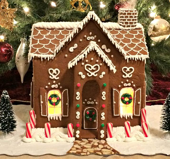 an elaborately decorated gingerbread house in front of a Christmas tree