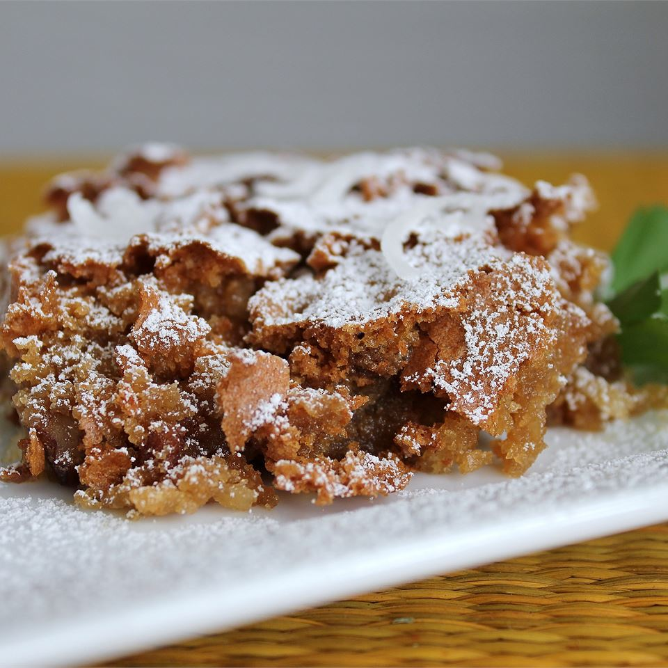slice of crumbly chocolate cake with powdered sugar sprinkled over the top