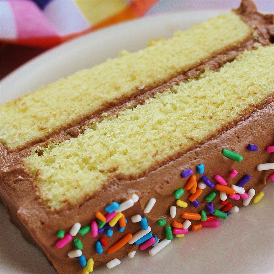 slice of yellow cake with chocolate frosting and candy sprinkles