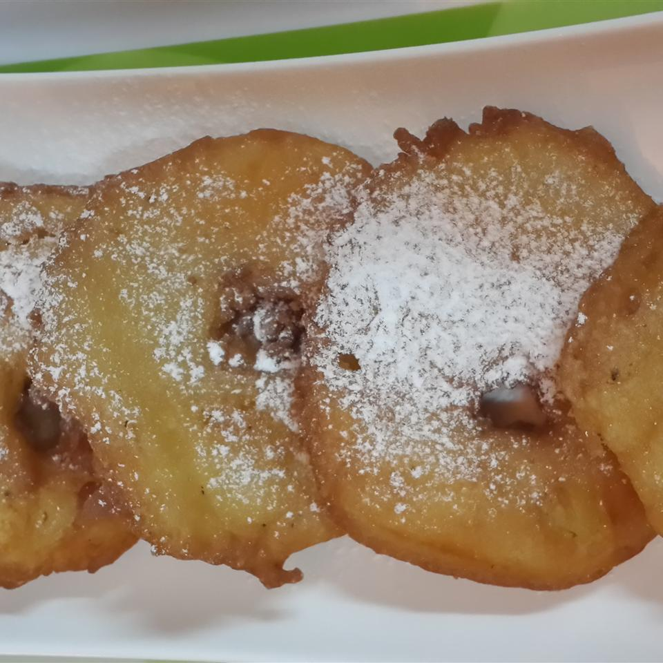 Apple fritter rings with powdered sugar on white platter