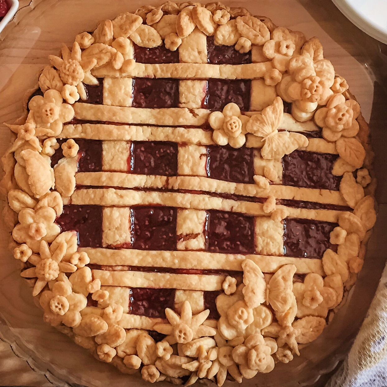 overhead view of berry pie decorated with pie crust strips and floral cutouts
