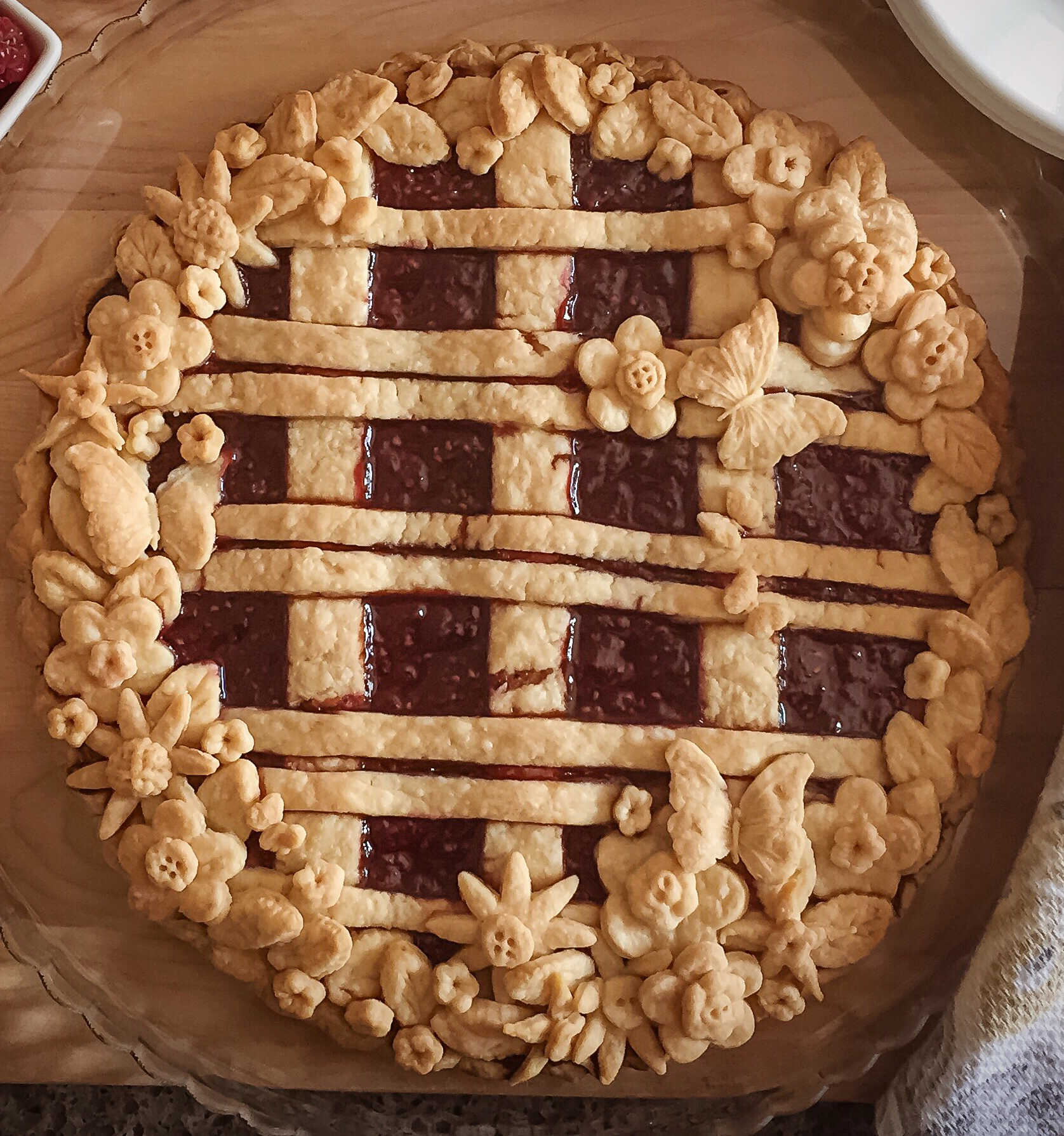 a top-down view of an intricately decorated pie with a double lattice crust and flower and butterfly cutouts around the edges and on the lattice