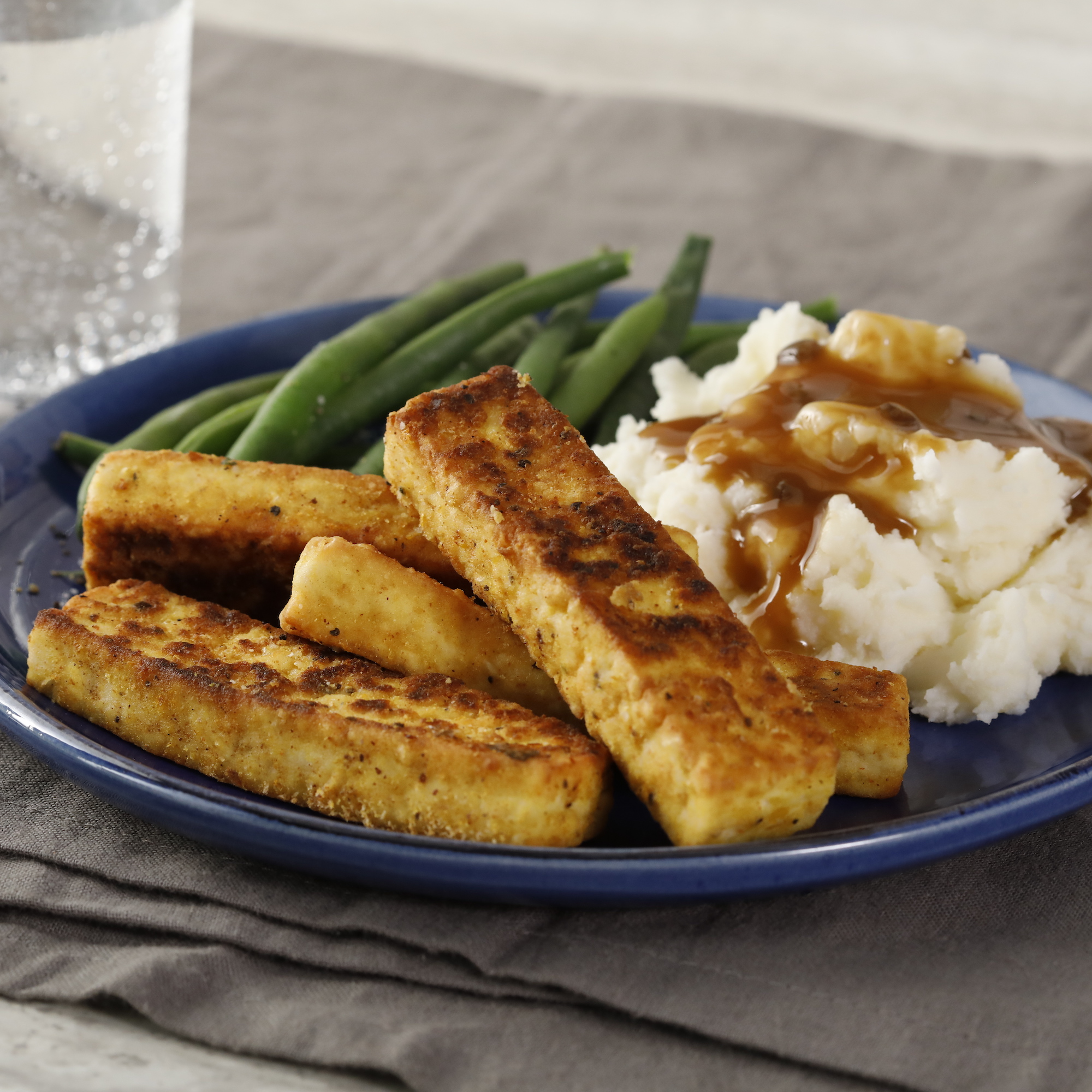 fried tofu slices on plate with mashed potatoes and green beans