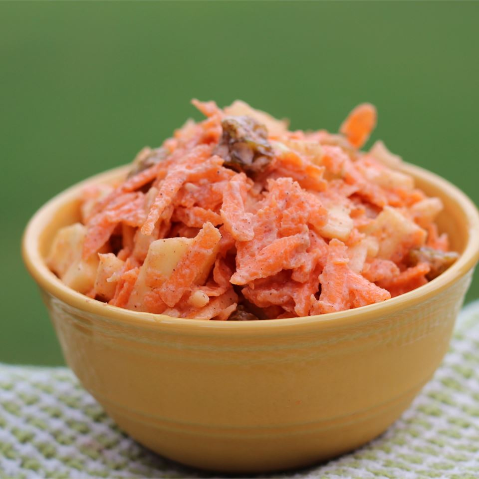 Carrot, apple, and raisin salad in a yellow bowl