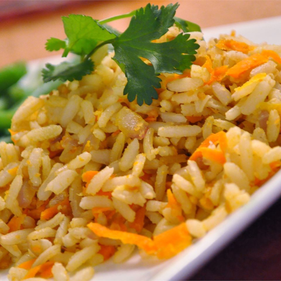 Carrot Rice on a white dish with parsley garnish