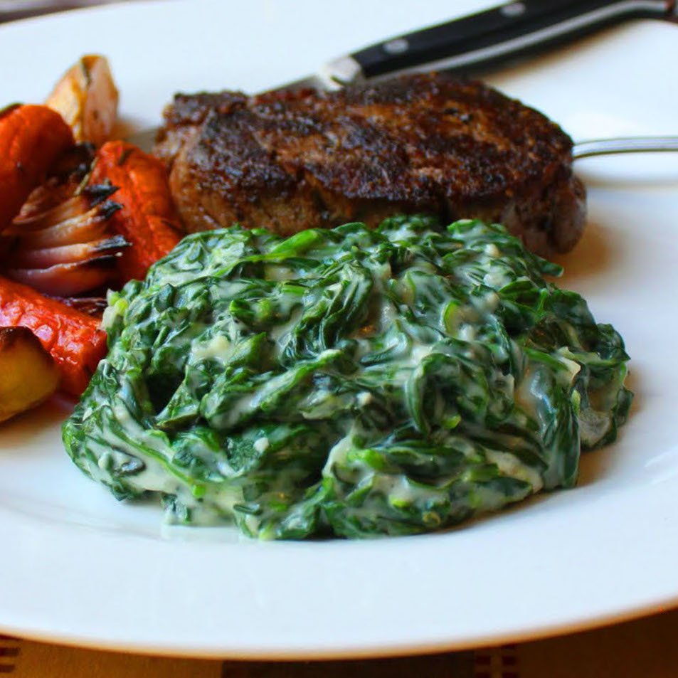 creamed spinach on a plate with steak and roasted vegetables