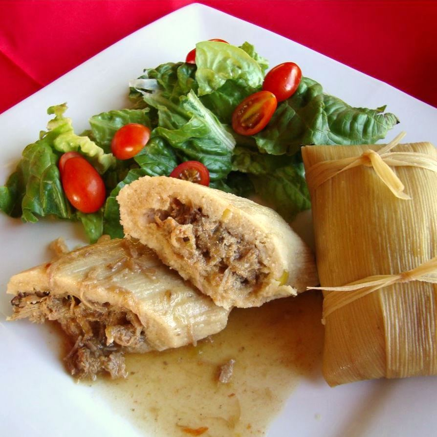 tamales on a white plate with salad on the side
