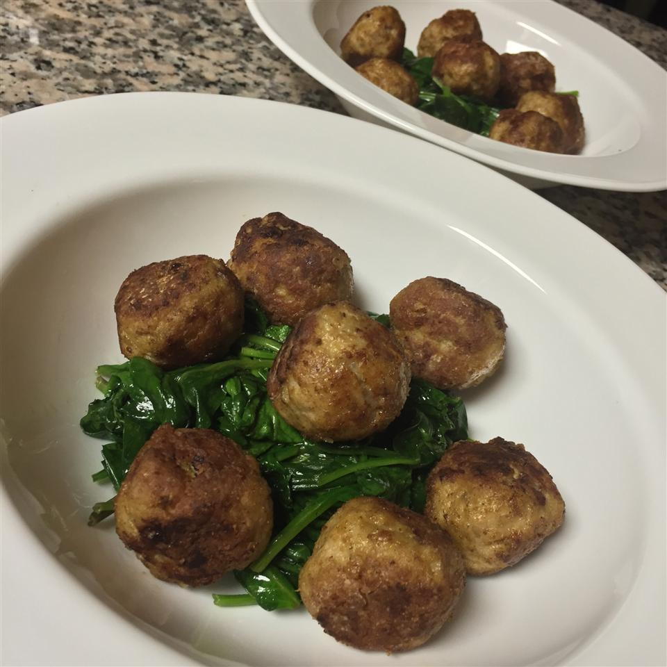 Curried Turkey Meatballs on a white plate with spinach