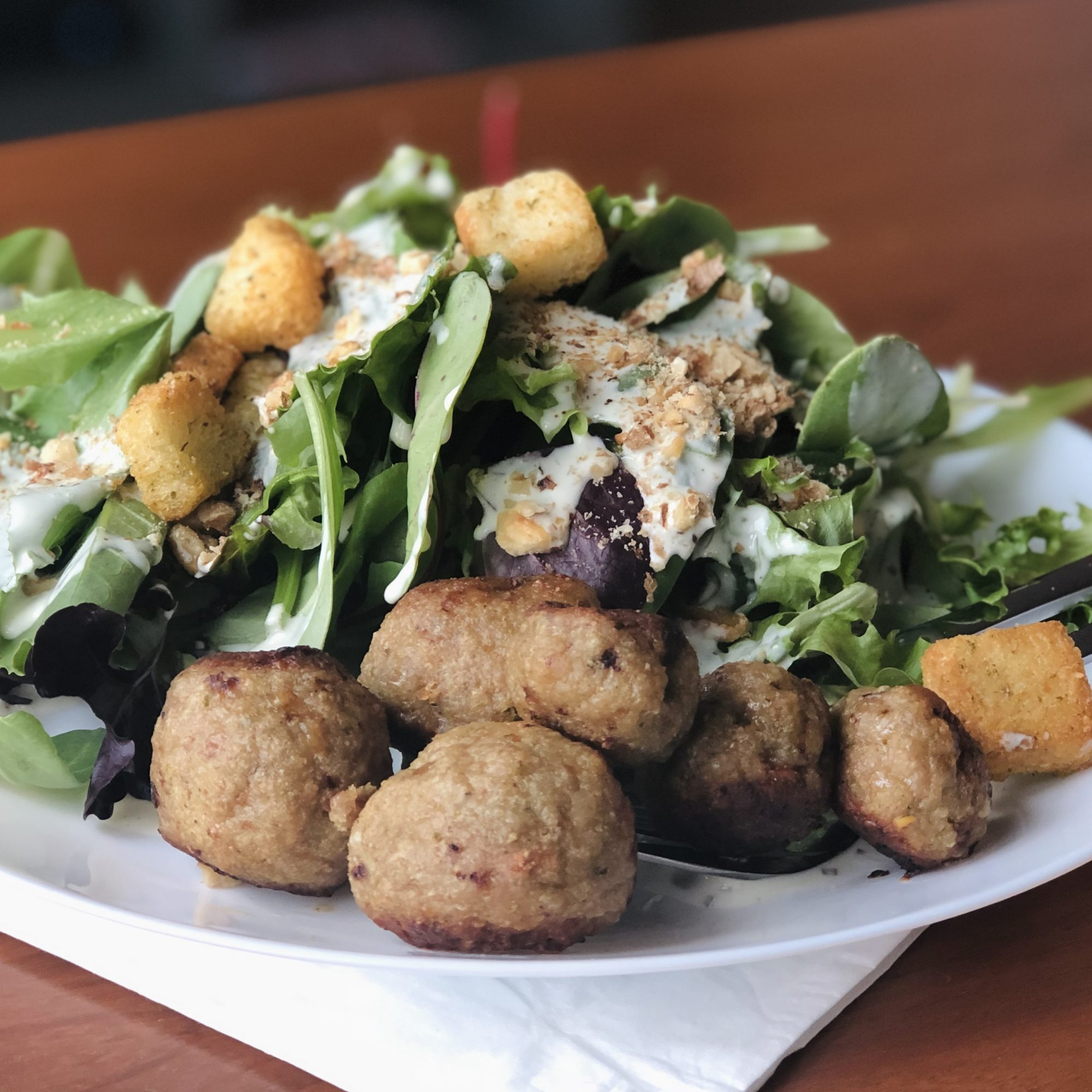 Pesto Turkey Meatballs on a plate with salad