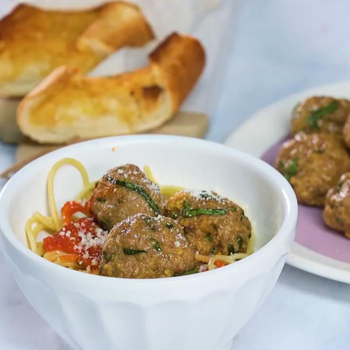 Baked Turkey Meatballs in a white bowl with spaghetti