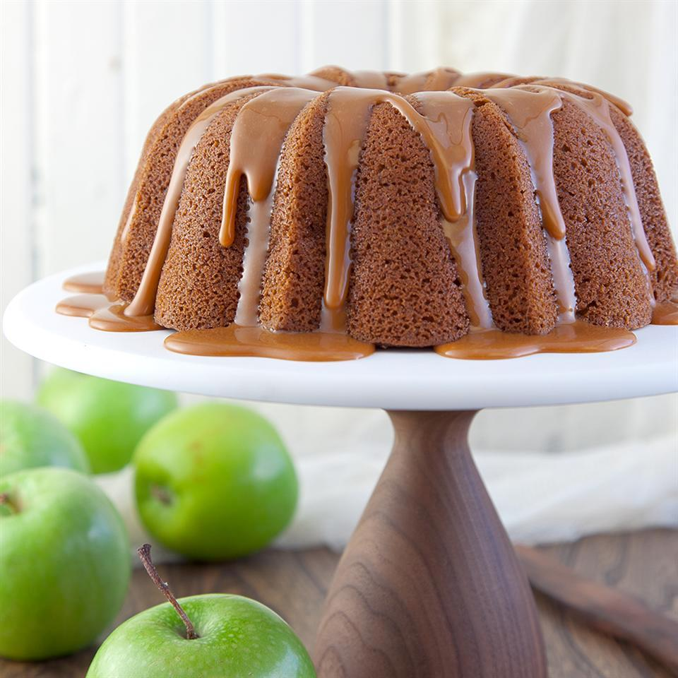apple pound cake on a cake stand beside apples