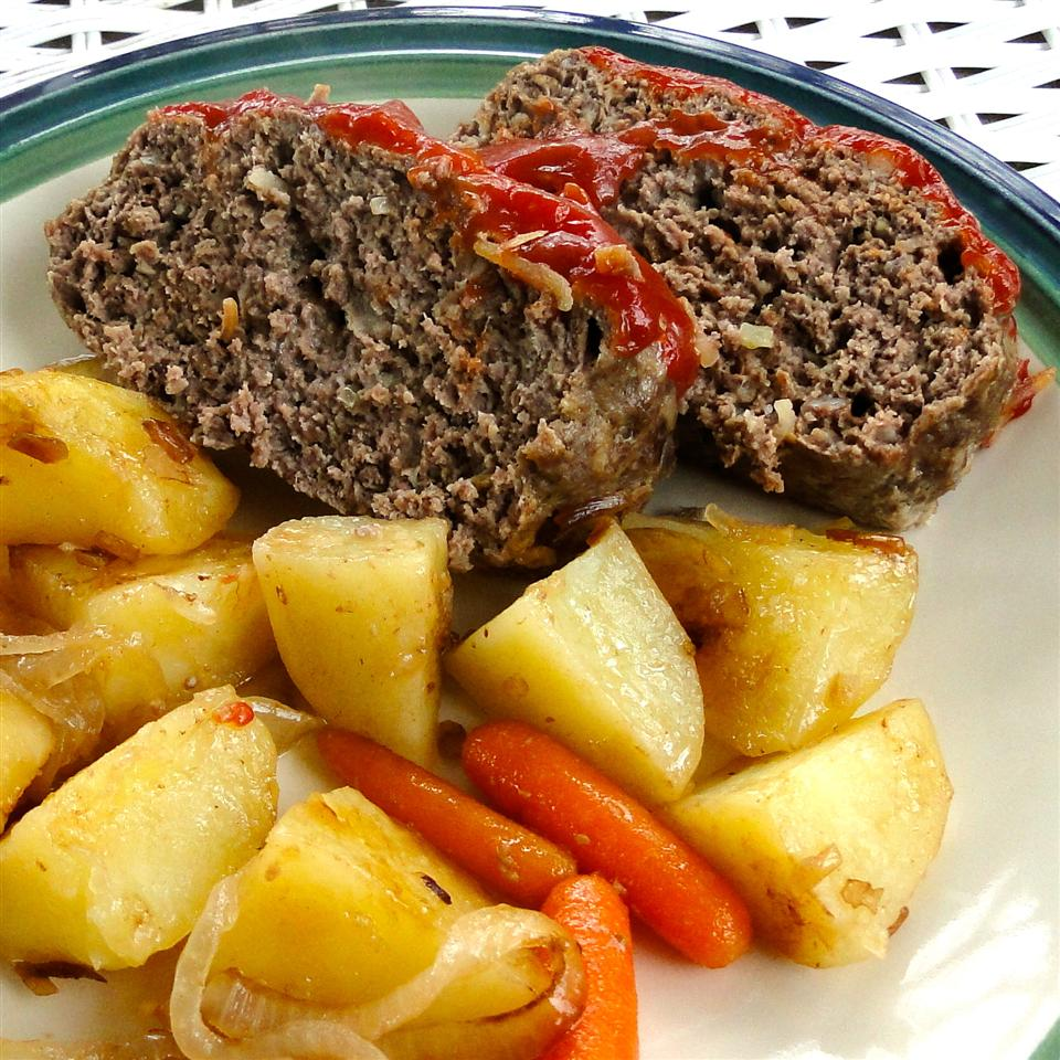 Meatloaf slices, gold potatoes, carrots, and onion on white plate