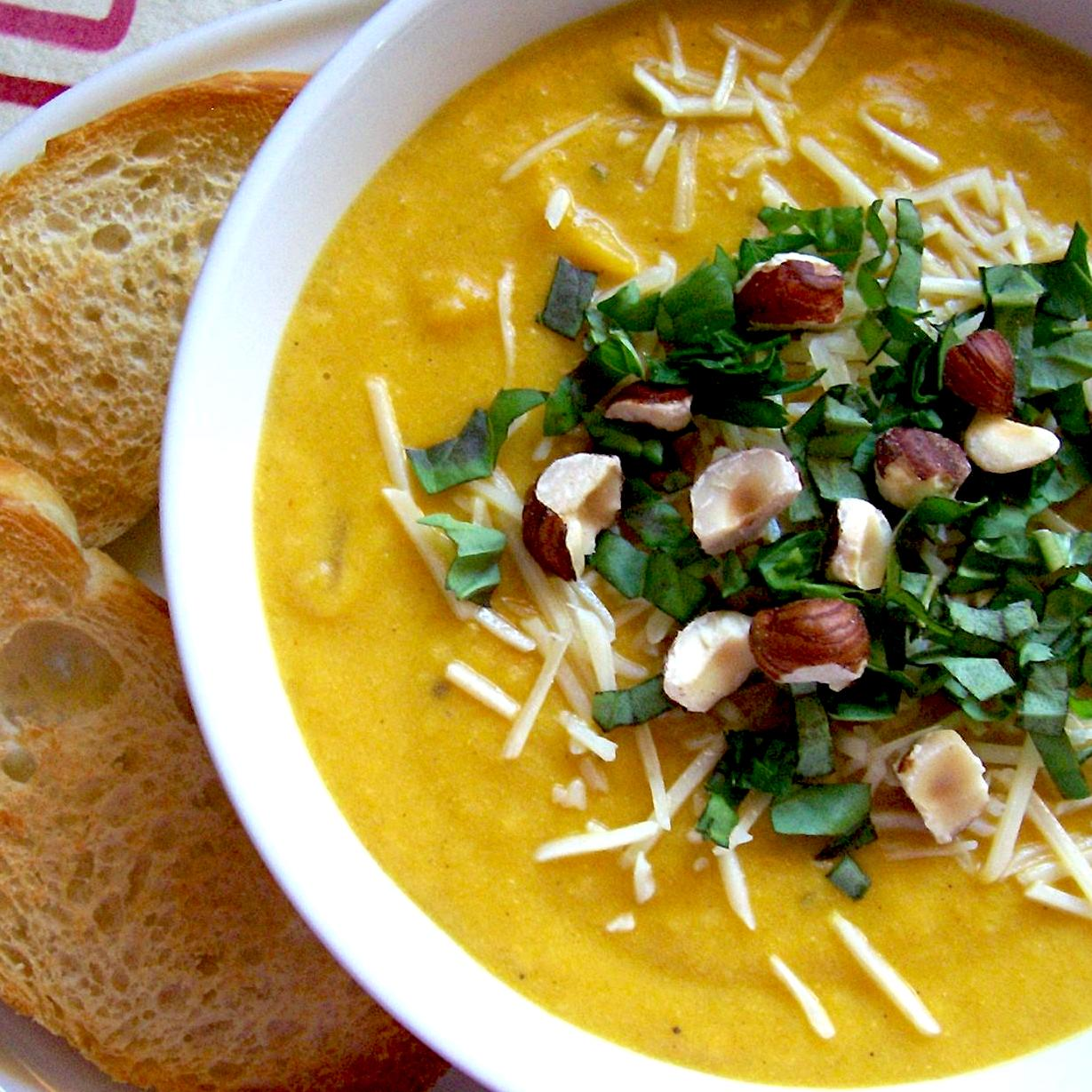 butternut squash soup in a while bowl with hazelnuts and cheese on top