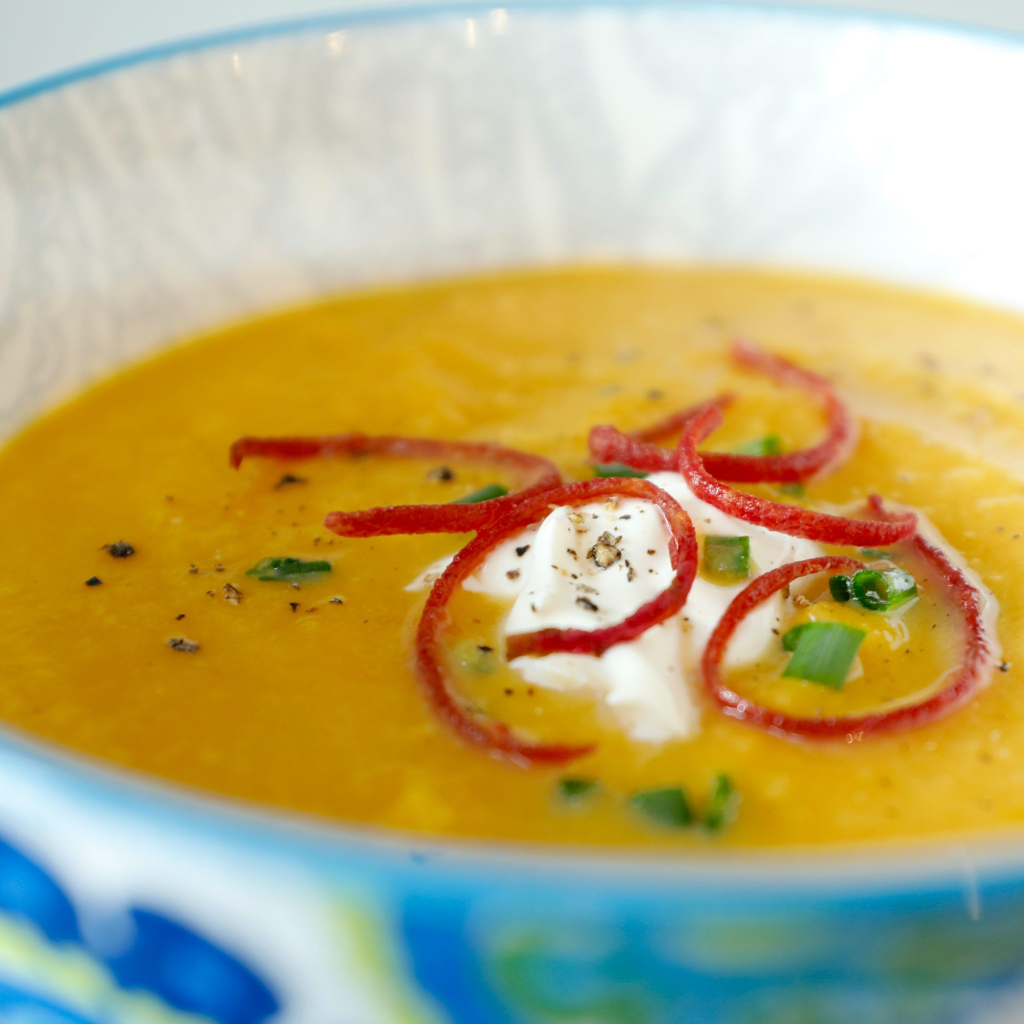 butternut squash soup with sour cream garnish in a blue and white bowl