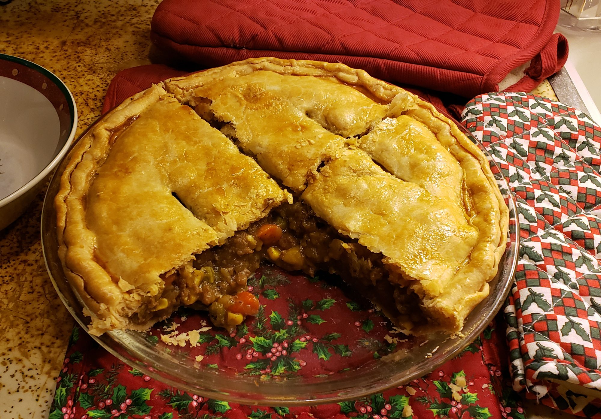 A cut open two-crust meat pie showing a filling of ground beef, carrots, and potatoes
