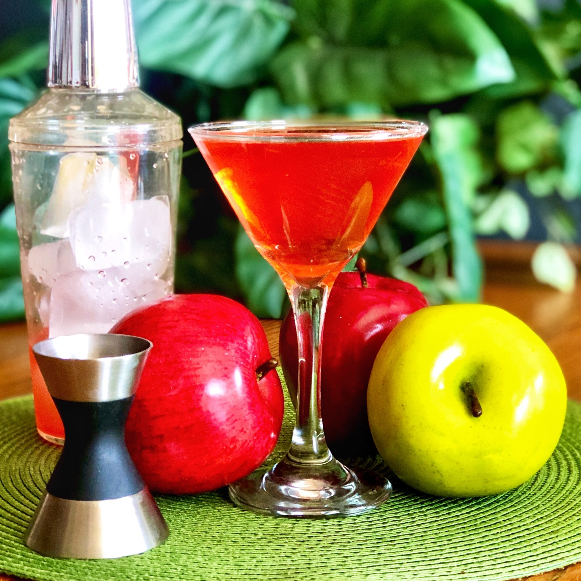 red apple martini in a glass with apples on the side