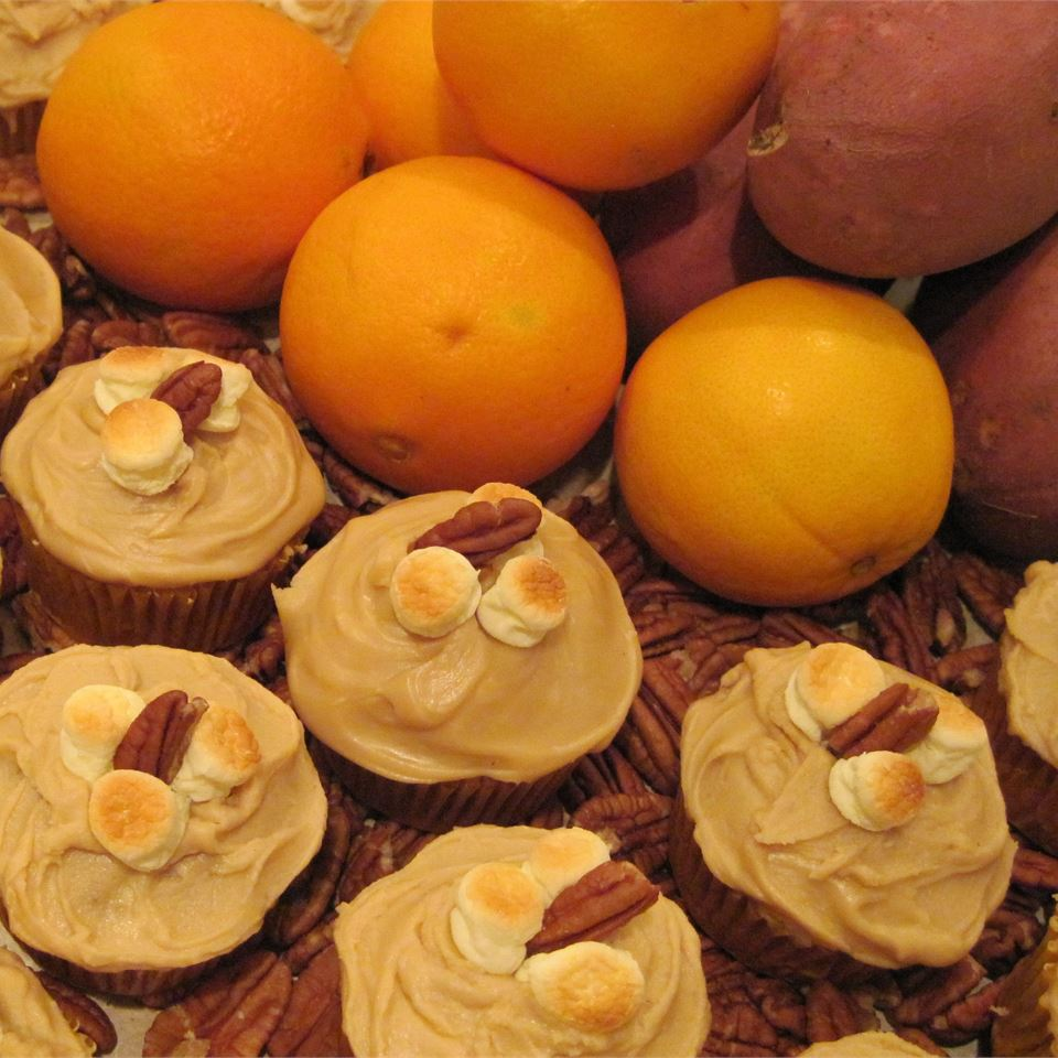 Cupcakes with toasted marshmallows and pecans next to oranges and sweet potatoes
