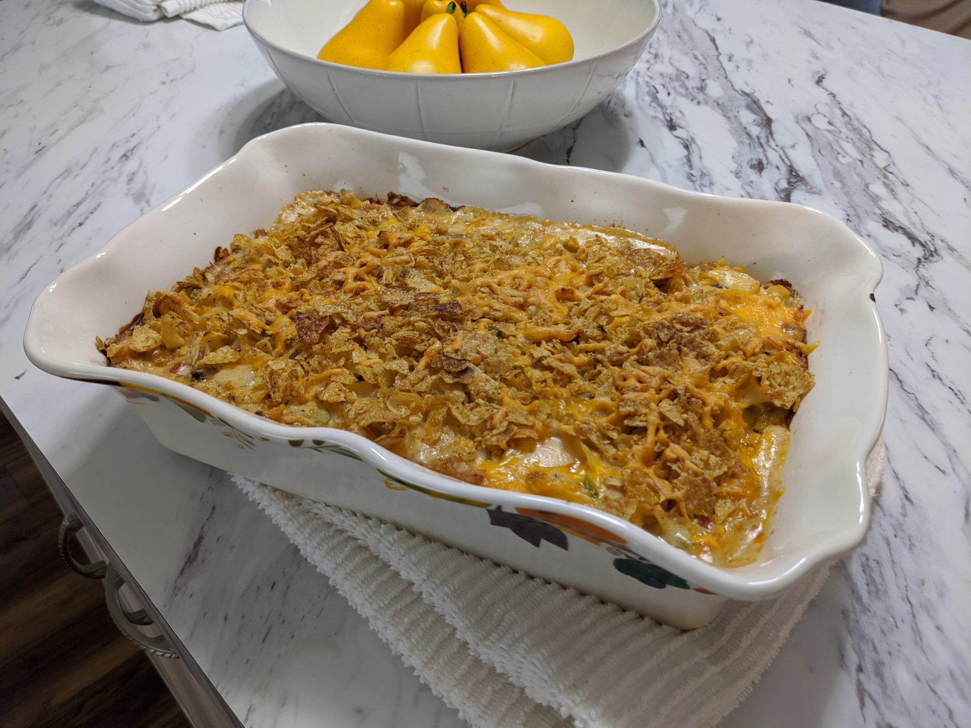 Turkey and noodle casserole in white dish on marble counter top