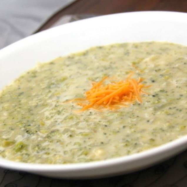 cream of broccoli soup in a white bowl with sprinkle of cheese on top