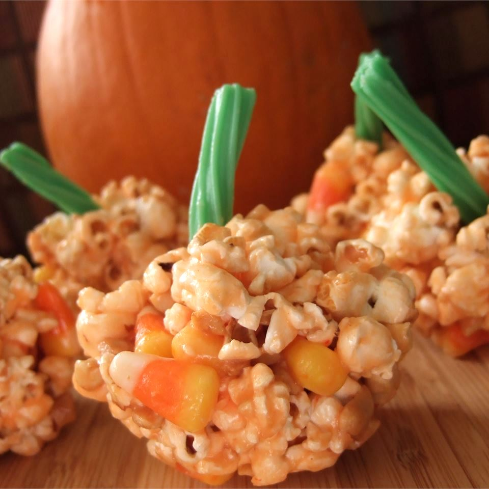 orange-colored popcorn shaped like pumpkins with candy stems