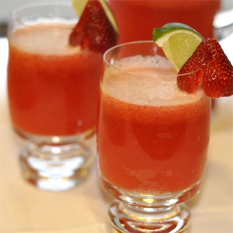 two glasses of Strawberry Beer Margaritas with lime and strawberry garnish