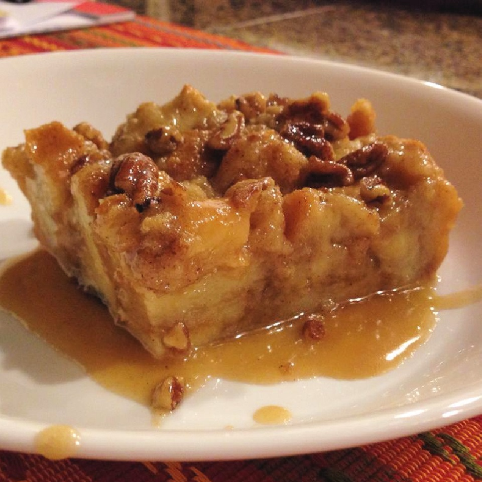 slice of bread pudding with praline sauce on a white plate