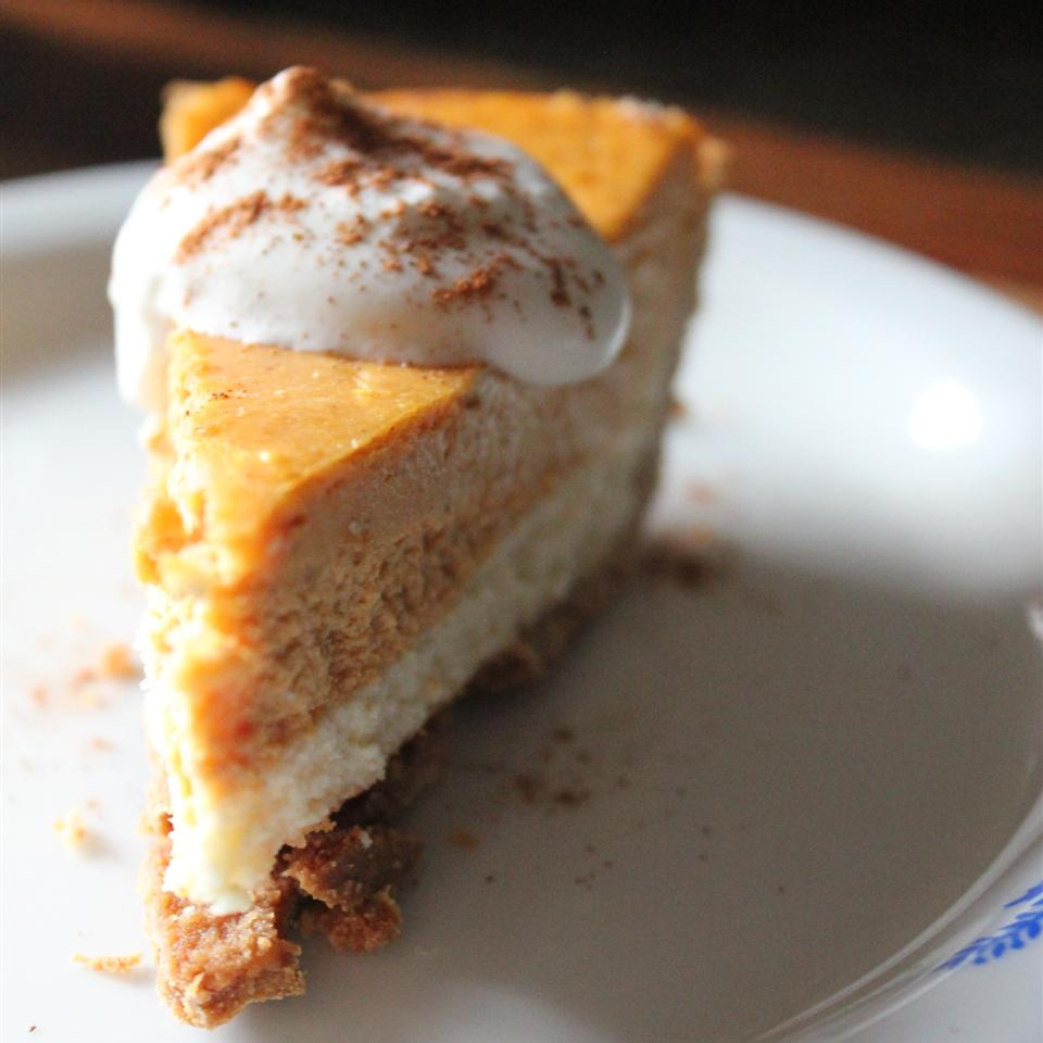 double layered pumpkin cheesecake on a plate with whipped cream topping
