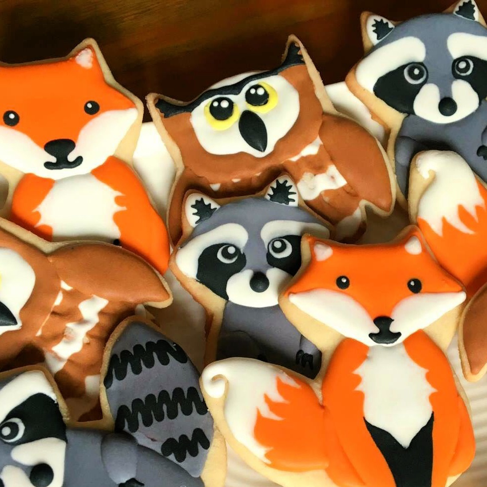 plate of cutout sugar cookies decorated like foxes, racoons, and owls